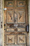 Old weathered door with padlock. And broken doorbell of abandoned, foreclosed home Royalty Free Stock Images