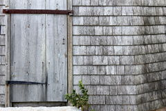 Old weathered door. Weathered wooden door with rusted hinge and locked with rusted metal bar against weathered wooden siding Royalty Free Stock Photography