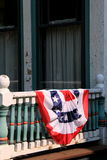 Old,weathered exterior of home with American flag draped over railing Royalty Free Stock Images