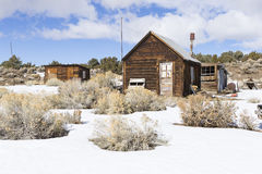 Old weathered Ghost Town buildings in the desert during winter with snow. Stock Photos