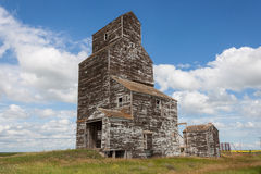 Old Weathered Grain Elevator with Blue Sky and Clouds Royalty Free Stock Images