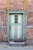 Old, weathered, green wooden door. In a half-timbered house with red bricks royalty free stock image