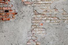 Old and weathered grungy broken red brick wall from abandoned house partly covered old cement with peeling coating background. Old and weathered grungy broken royalty free stock image