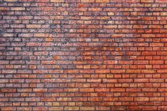 Old and weathered grungy red brick wall marked by the long exposure to the elements as surface texture background.  stock image