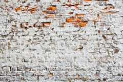 Old and weathered grungy red brick wall partly painted with white peeling paint and covered by old cement as texture background.  stock image
