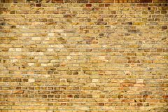 Old and weathered grungy yellow and red brick wall as seamless pattern texture wall background royalty free stock images