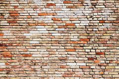 Old and weathered grungy yellow and red brick wall with visible crack as rustic rough texture background royalty free stock image