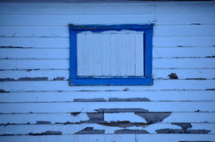 Old weathered house with flaking paint and window Stock Image