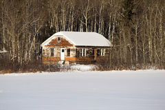 An old, weathered house in a forest. An old, abandoned house with a snow topped roof in a forest Stock Photos