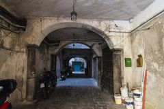 Old interior passage in Palermo in Sicily, Italy. Old and weathered interior passage with parked motorbikes giving access to housing in the old town of Palermo Stock Photography