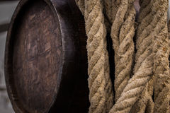 Old weathered liquer barrel next to hemp rope. An old weathered barrel and a worn rope hanging side by side Royalty Free Stock Images