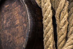 Old weathered liquer barrel next to a used hemp rope. An old weathered barrel and a worn rope hanging side by side Stock Photo