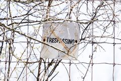 Old and weathered No trespassing sign posted to wire fence, safe Royalty Free Stock Photography