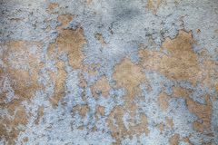 Old weathered paint layer on old concrete wall. Aged abandoned grey yellow street wall textured background stock photography