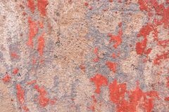 Old weathered painted wall background texture. Red dirty peeled plaster wall with falling off flakes of paint. Old weathered painted wall texture background royalty free stock photo