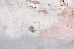 Old weathered painted wall background texture. White dirty peeled plaster wall with falling off flakes of paint. stock photography
