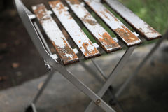 Old weathered peeling paint white outdoor chair in garden Stock Images