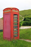 Old weathered phonebox at the coast Stock Photos