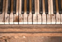Old and Weathered Piano Keys. The keys of an old weathered upright piano, that sits artistically at a corner of downtown Colorado Springs. They are pealed and Stock Photo