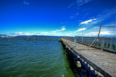 A old weathered pier with a chain link fence HDR Stock Photos