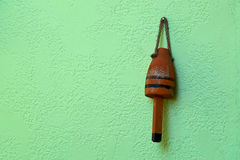Old weathered red buoy on green wall Stock Photos