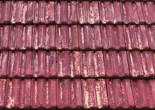 Old and weathered red stone roof tiling in macro closeup with faded out colors, a architecture texture background. Some old and weathered red stone roof tiling stock photos