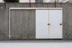 Roll up garage door on brick wall. Old weathered roll up garage door on brick wall stock photo