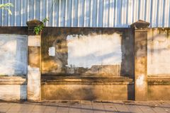 Old weathered rustic concrete wall and fence along sidewalk in f Stock Images