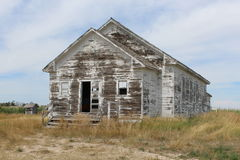 Old weathered schoolhouse in Nebraska. Weathered white old schoolhouse with outhouse in a cornfield Stock Photography