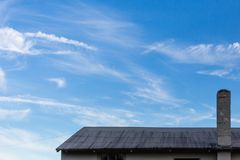 Old weathered shingle roof blue sky. Old shingle roof concrete chimney blue cloudy sky Stock Photo