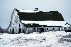 Old weathered snow covered barn. This old barn sits covered in snow struggling to continue standing Stock Image