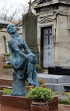 Old, weathered statue standing near graves of historic Pere Lachaise Cemetery,Paris,France,2016. Old,weathered statue of woman weeping as she sits near grave of royalty free stock photos