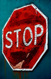 Old weathered stop sign on teal background. Old weathered stop sign, paint cracked and peeling off, on teal background stock photos