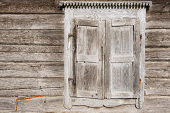 Old weathered traditional wooden window shutters. Royalty Free Stock Images
