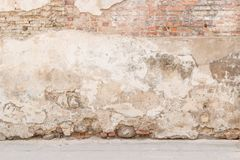 Old weathered vintage brick wall with broken plaster and pavement on the ground. Grungy urban background. royalty free stock photo