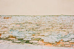 Old weathered vintage brick wall with broken plaster and pavement. Grungy urban background. Royalty Free Stock Image