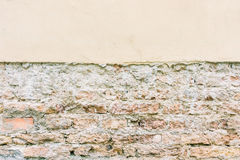 Old weathered vintage brick wall with broken plaster and pavement. Grungy urban background. Royalty Free Stock Photos
