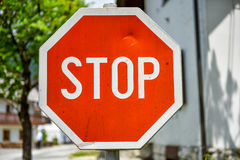 Old, weathered and violated stop sign in the street Royalty Free Stock Images