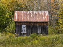 Old Weathered Wood Shack with Two Windows - One with Glass, One Closed Up Royalty Free Stock Photography