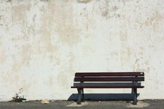 An old weathered wooden bench against a white washed wall Royalty Free Stock Photography