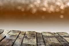 Old weathered wooden board or rustic table top with a sparkling bokeh of golden party lights in the background royalty free stock image