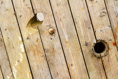 Old weathered wooden boards with holes on the surface. Texture of natural wood. Abstract background Stock Photos