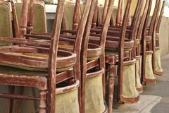 Piled up chairs. Old weathered wooden chairs piled up outside stock photo