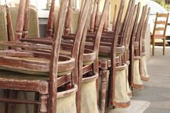 Piled up chairs. Old weathered wooden chairs piled up outside royalty free stock image