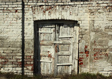 Old weathered wooden door in brick wall Stock Photography
