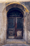 Old weathered wooden door, closed house entrance. Weathered wooden door, closed house entrance. Detail from old european town Stock Photos