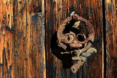 Old and weathered wooden door and rusted iron knocker Stock Photography