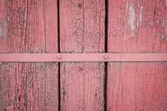 Old weathered wooden plank painted in living coral, pink color with metal strip, wooden texture wall background.  stock images