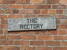 Old weathered wooden Rectory sign on a brick wall. An old wooden weathered church Rectory sign on a brick wall Royalty Free Stock Photography