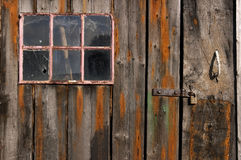 Old weathered and worn wooden planks with door and pink framed window Royalty Free Stock Images